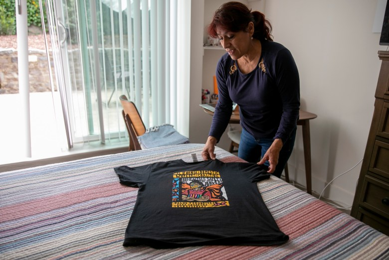 Martha Garrido lays out a California Domestic Worker's Coalition shirt on the bed at her San Francisco home. Garrido says she was able to avoid falling behind on rent after breaking her hand earlier this year because her landlord gave her a break while she was unable to work. Photo by Anne Wernikoff, CalMatters
