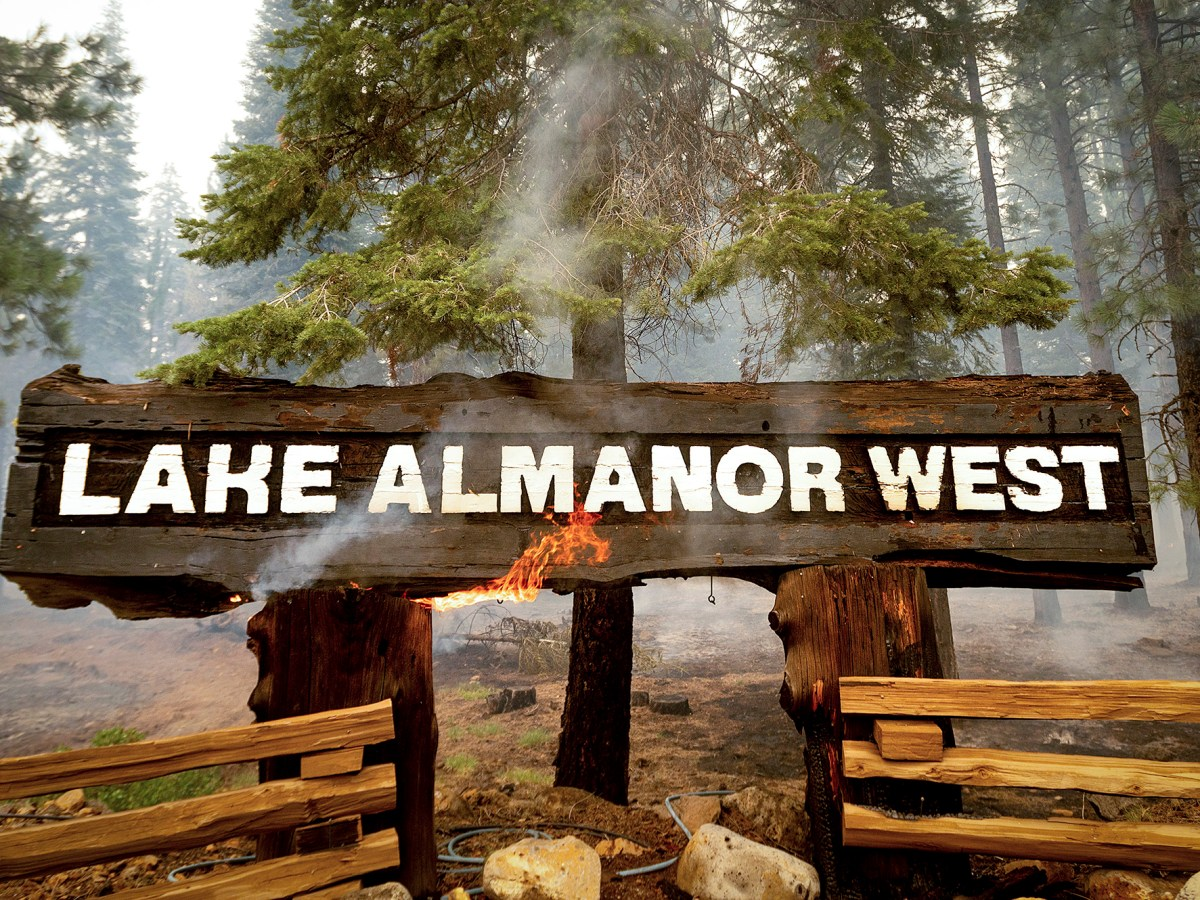Flames on an entrance sign for Lake Almanor West as the Dixie Fire burned in Plumas County on Aug. 5, 2021. AP Photo/Noah Berger