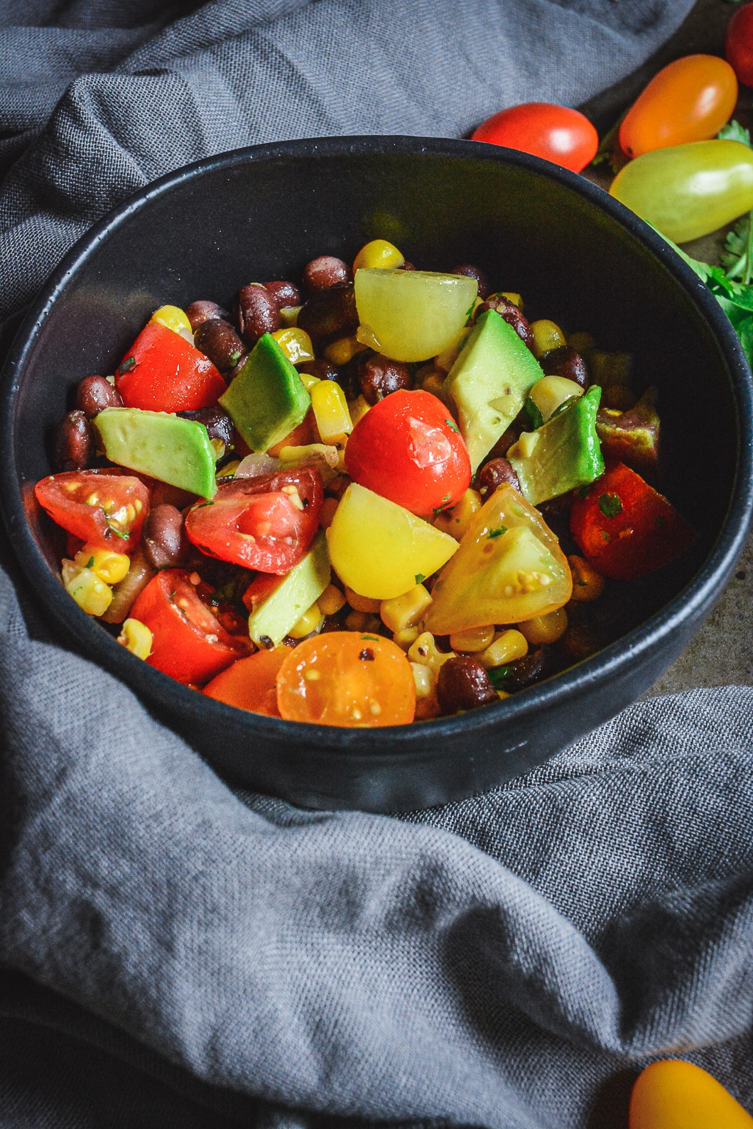 Mexican Tomato Salad with Black Beans, Corn, and Avocado in black bowl with tomatoes