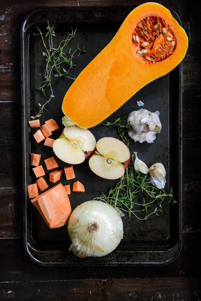 Roasting tray with half of butternut squash, cut up sweet potato, garlic, onion, apple and greens