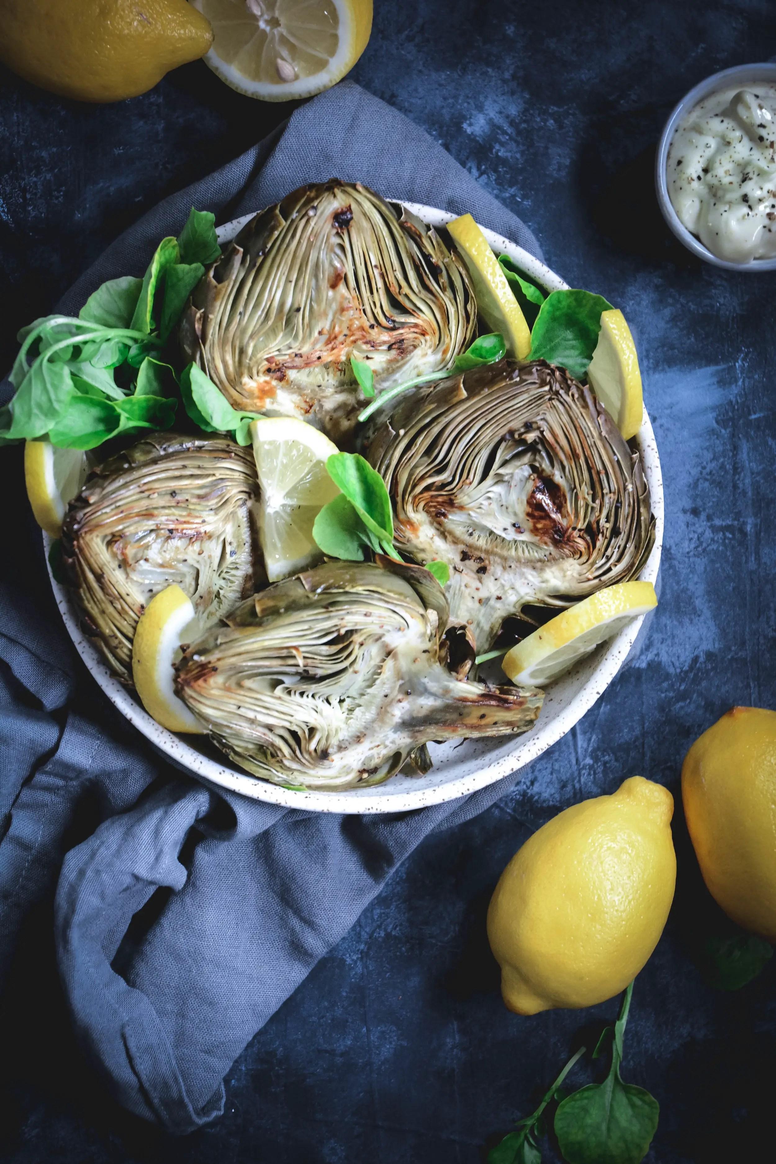 roasted artichoke halves with lemon slices in bowl