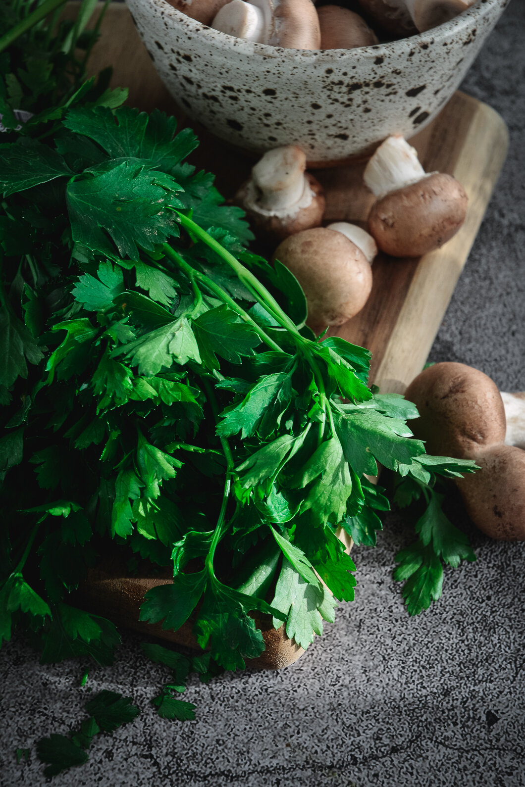 Mushrooms in bowl with parsley on cutting board