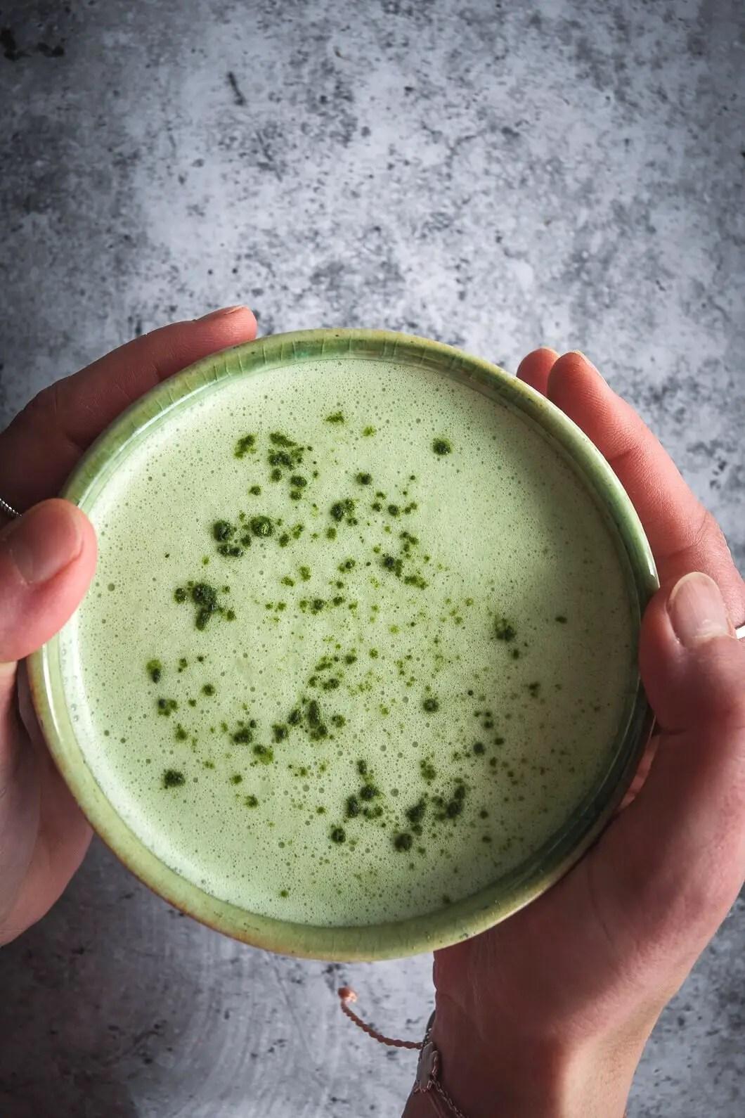 Matcha and moringa latte in mug held between hands