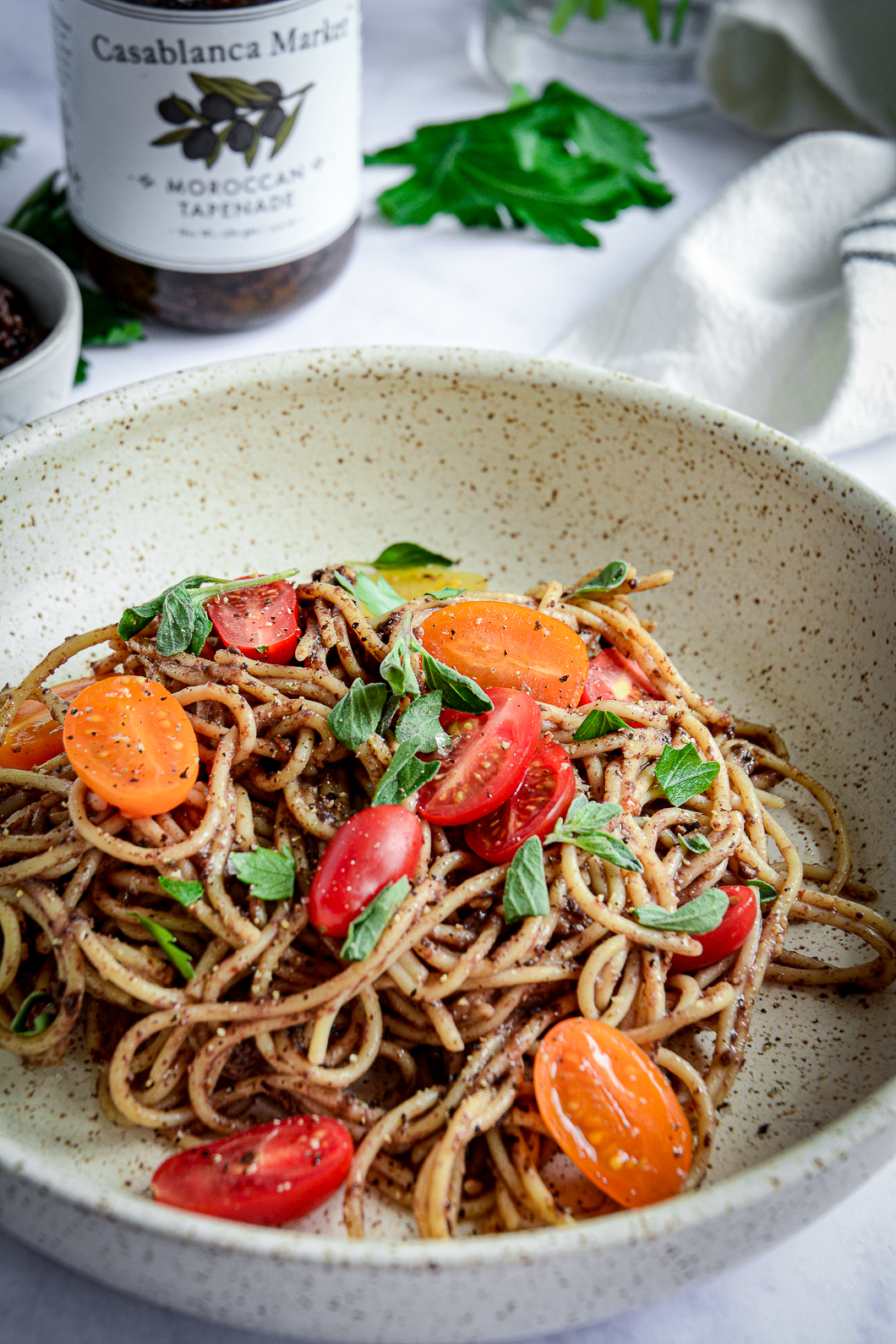 Moroccan Tapenade Spaghetti with Tomatoes and Herbs with herbs and jar of tapenade