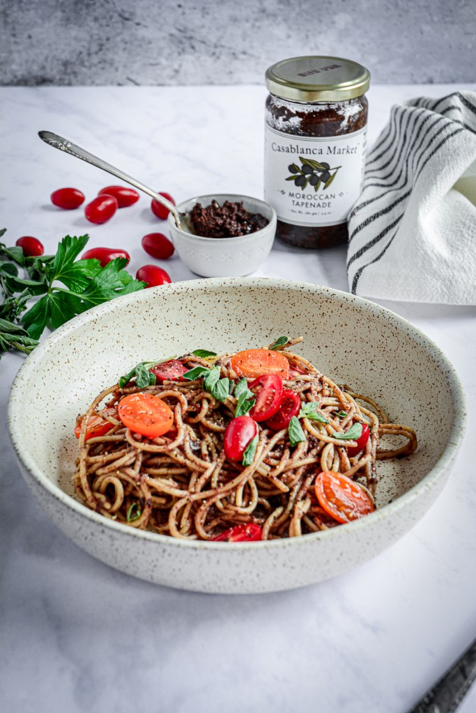 Moroccan Tapenade Spaghetti with Tomatoes and Herbs in bowl with jar of tapenade, bowl of tapenade, herbs and tomatoes