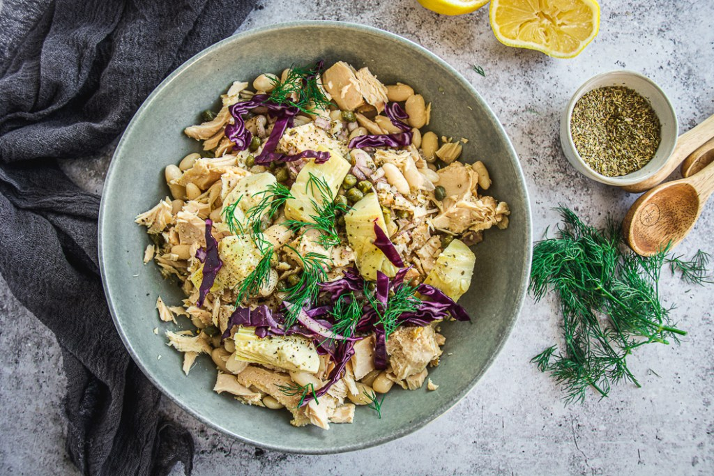 White bean tuna salad with artichoke hearts in bowl with dark colored napkin and lemons