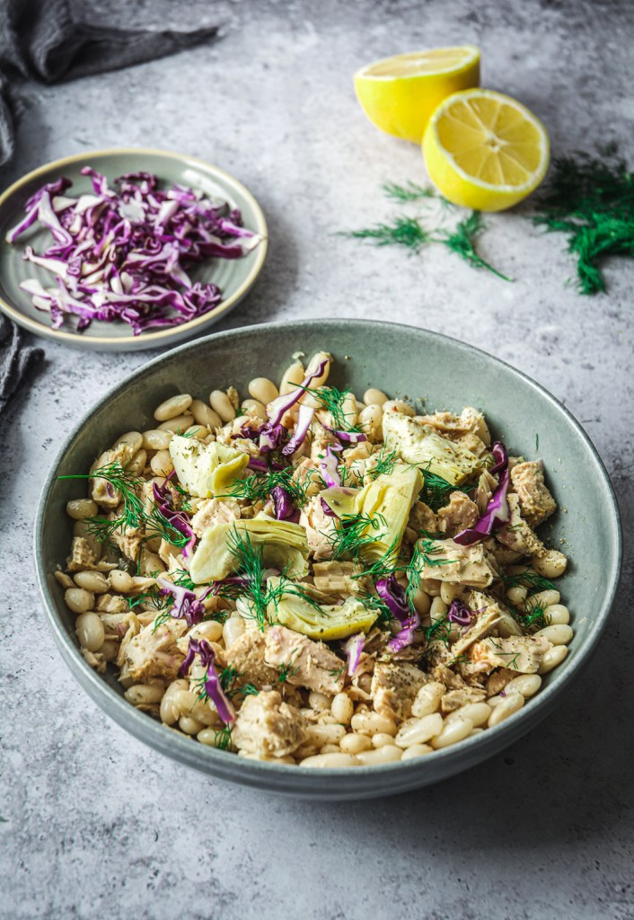 White Bean Tuna Salad with Artichoke Hearts in bowl, sliced cabbage and lemon halves