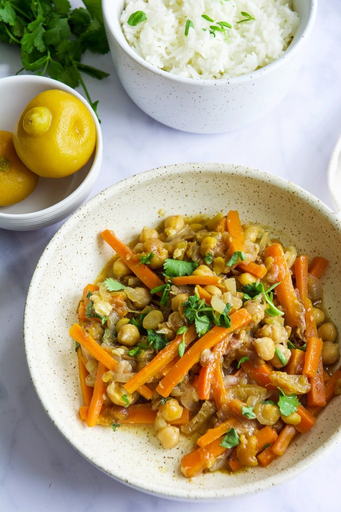 Moroccan Chickpea Tagine with Preserved Lemons in bowl with cilantro and preserved lemons in bowl in background