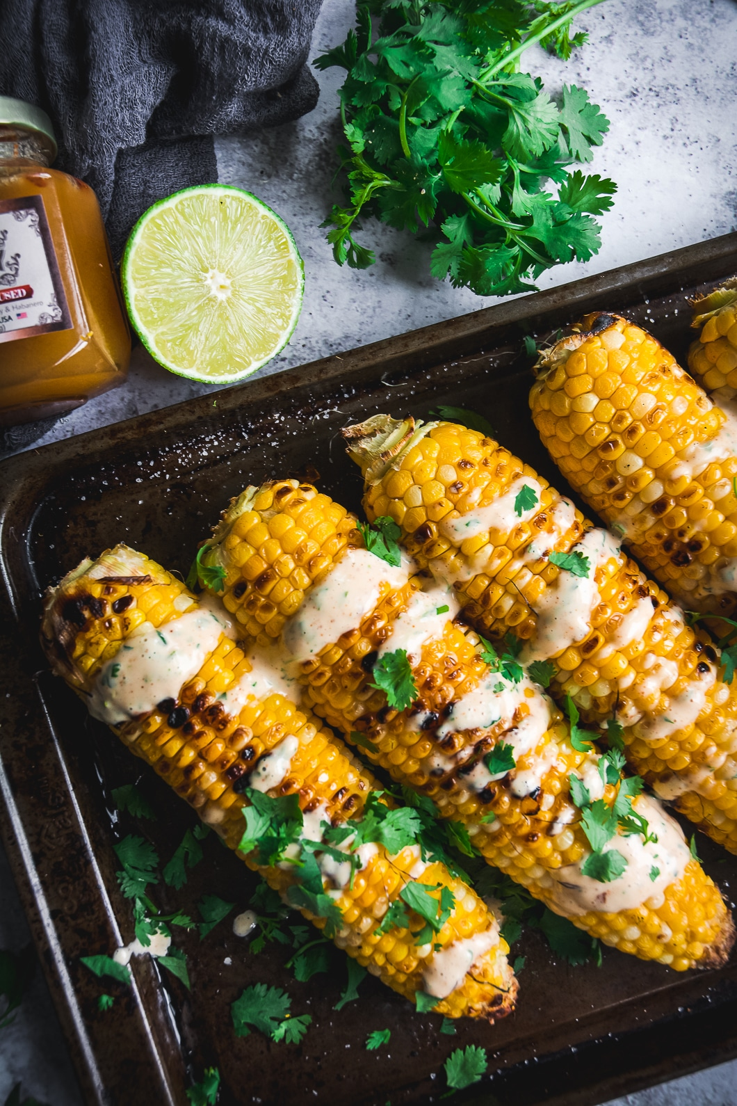 Grilled Corn with Spicy Habanero Honey Mayo drizzled over the corn with lime slice and cilantro