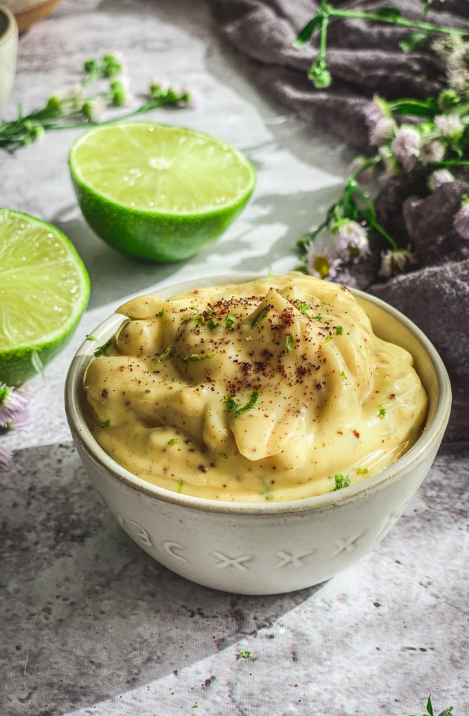 Chipotle Mayo in bowl on table with lime halves and grey napkin