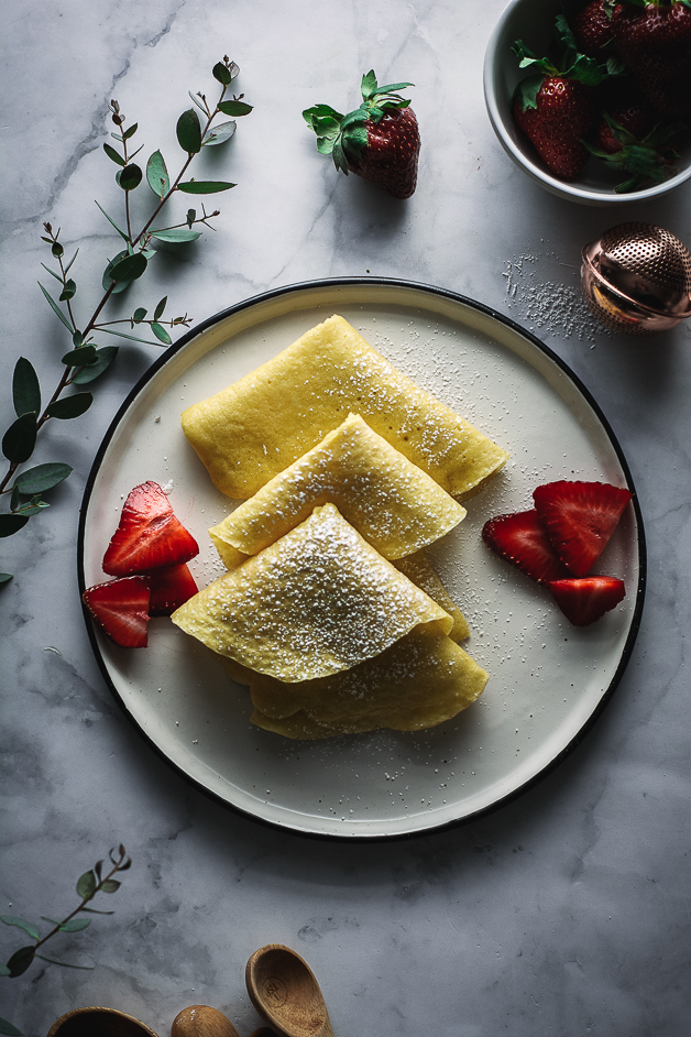 crepes in triangle shapes on plate with strawberries, eucalyptus