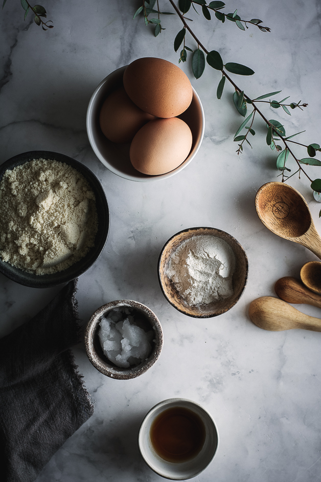small bowl of eggs, bowls of flour, eucalyptus branch and wooden spoons
