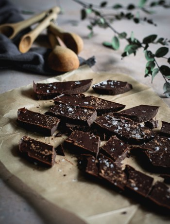chocolate chunks on parchment paper with wooden spoons and a green branch