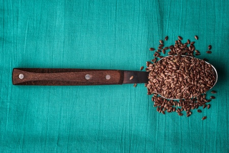 Image shows a turquoise background with a wooden handled spoon filled with brown flax seeds, as used in this recipe page on CALMERme.com