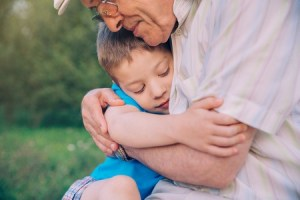 Image showing a young boy being cradled in a hug from a loved one and looking content, as described in this article on CALMERme.com