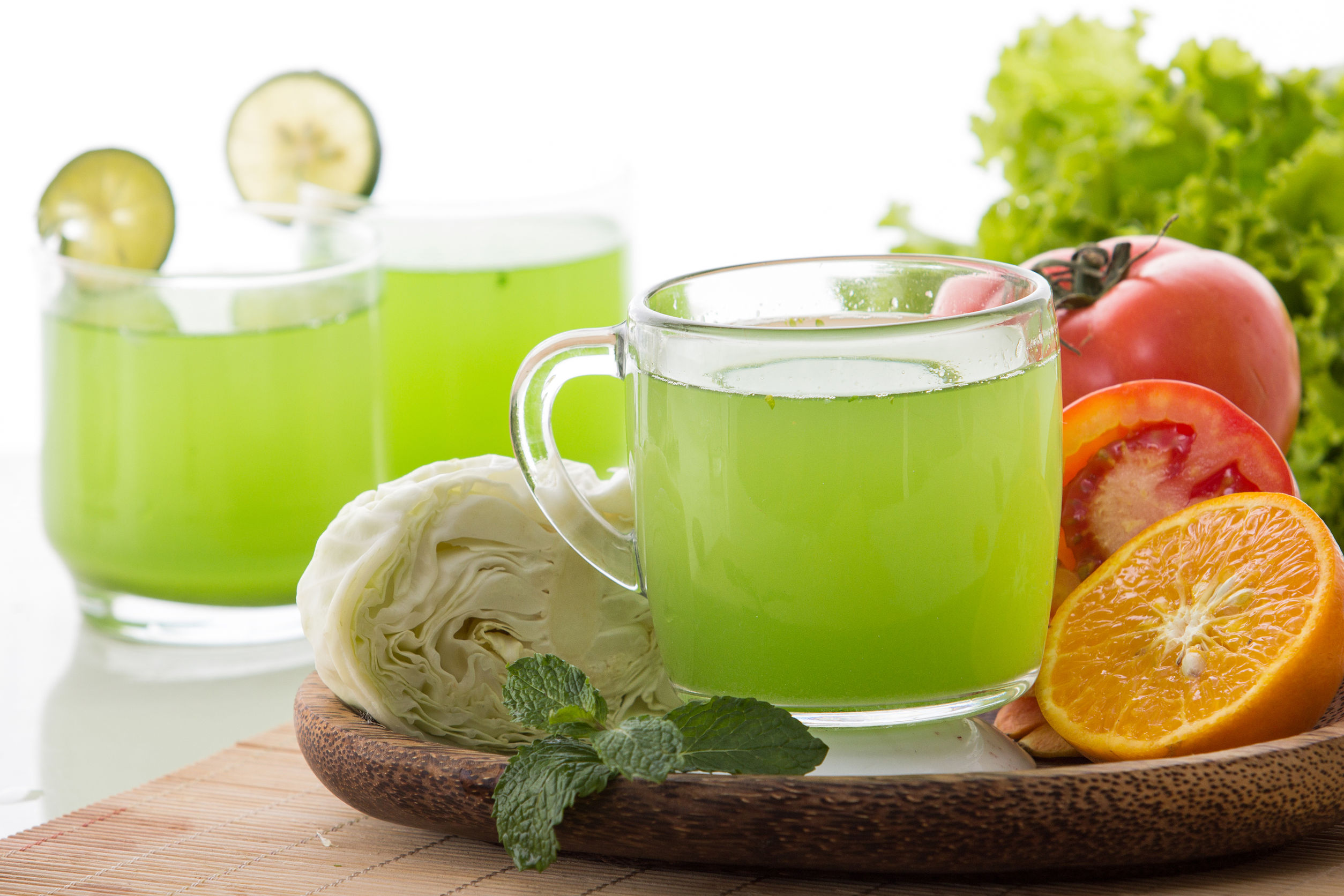 Image showing glass mugs filled with a clear delicious-looking pale green liquid, surrounded by fruits and vegetables indicating the ingredients you can include in a healthy juice drink, as described in this article on CALMERme.com