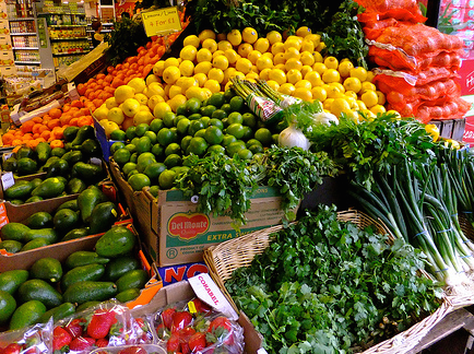 Image shows a market stall loaded with vegetables, such as might be used in the recipes described in this book review on CALMERme.com