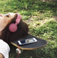 Image shows a woman taking some personal time to listen to music, as described in this post on CALMERme.com