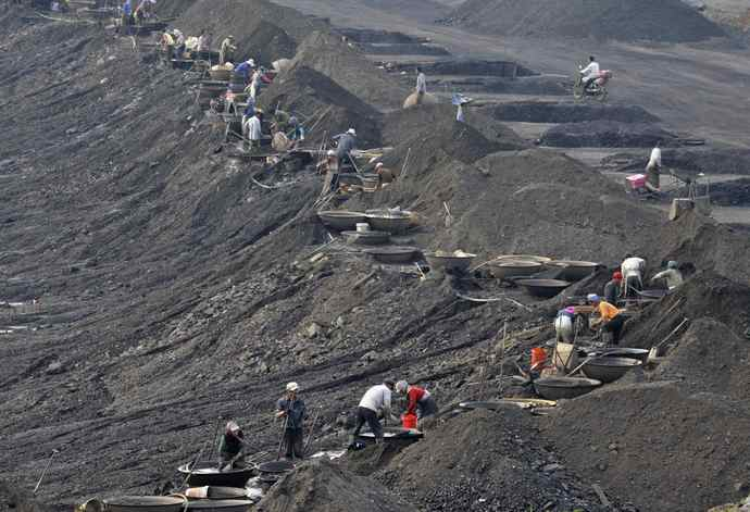 Labourers filter coal out of cinder at a dump site of Xilutian coal mine on the outskirts of Fushun