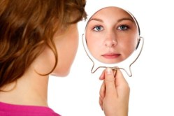 Girl Looking Through Mirror