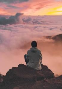 Chico meditando en una montaña