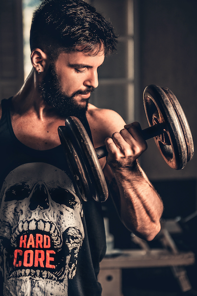 """Man lifting weights looking at his arm. Some men with HOCD will have doubts about their sexuality if they do not fit the mold of the stereotypical """"masculine guy."""" And just the same with women and femininity. However, this does not define your sexuality."""