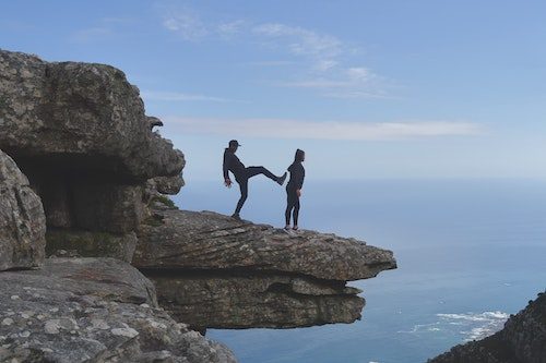 Man kicking a woman off a cliff. People with Harm OCD can fear that they will unintentionally harm someone.
