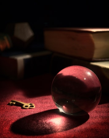 Picture of a key and a crystal ball on a table. We dont have the answers to life, and that's ok. Therapy for Existential OCD helps people learn to accept the uncertainty.
