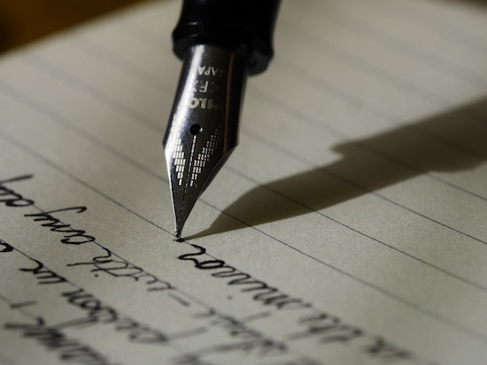 Quill tipped pen writing on lined paper. Writing out one's feared thoughts can be a great exposure to imagined or thought based fears. Get OCD treatment in California or online OCD counseling in Montana here.