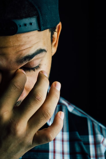 Exhausted and anxious man rubbing his eyes. Thought Action Fusion can make people believe their thoughts are real, can cause real things to happen to themselves or bad things to happen to others. Contact CalOCD for OCD treatment in Southern California or online therapy in California or Montana.