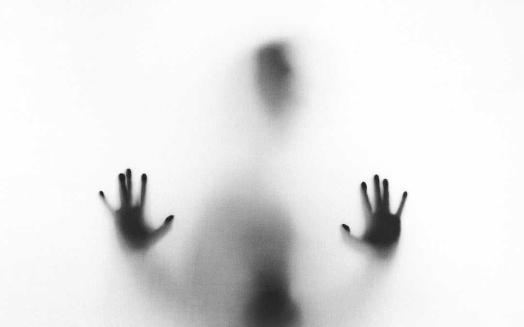Silhouette figure behind frosted glass screen with hands on glass