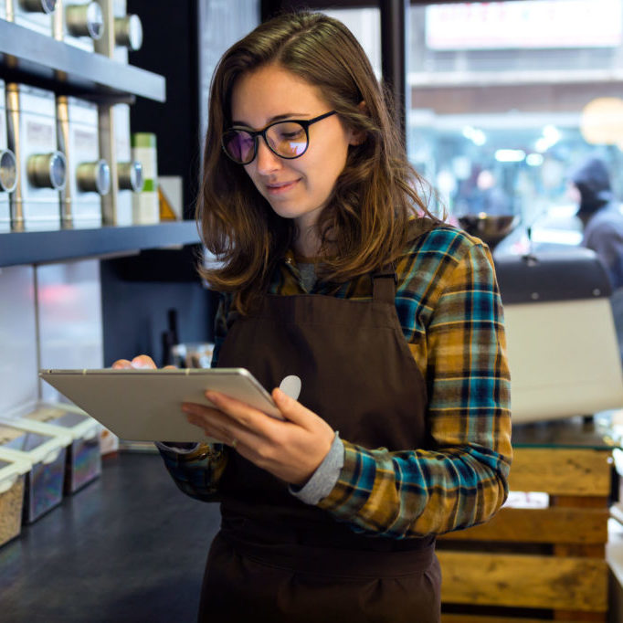 Portrait of beautiful young saleswoman doing inventory in a retail store selling coffee.