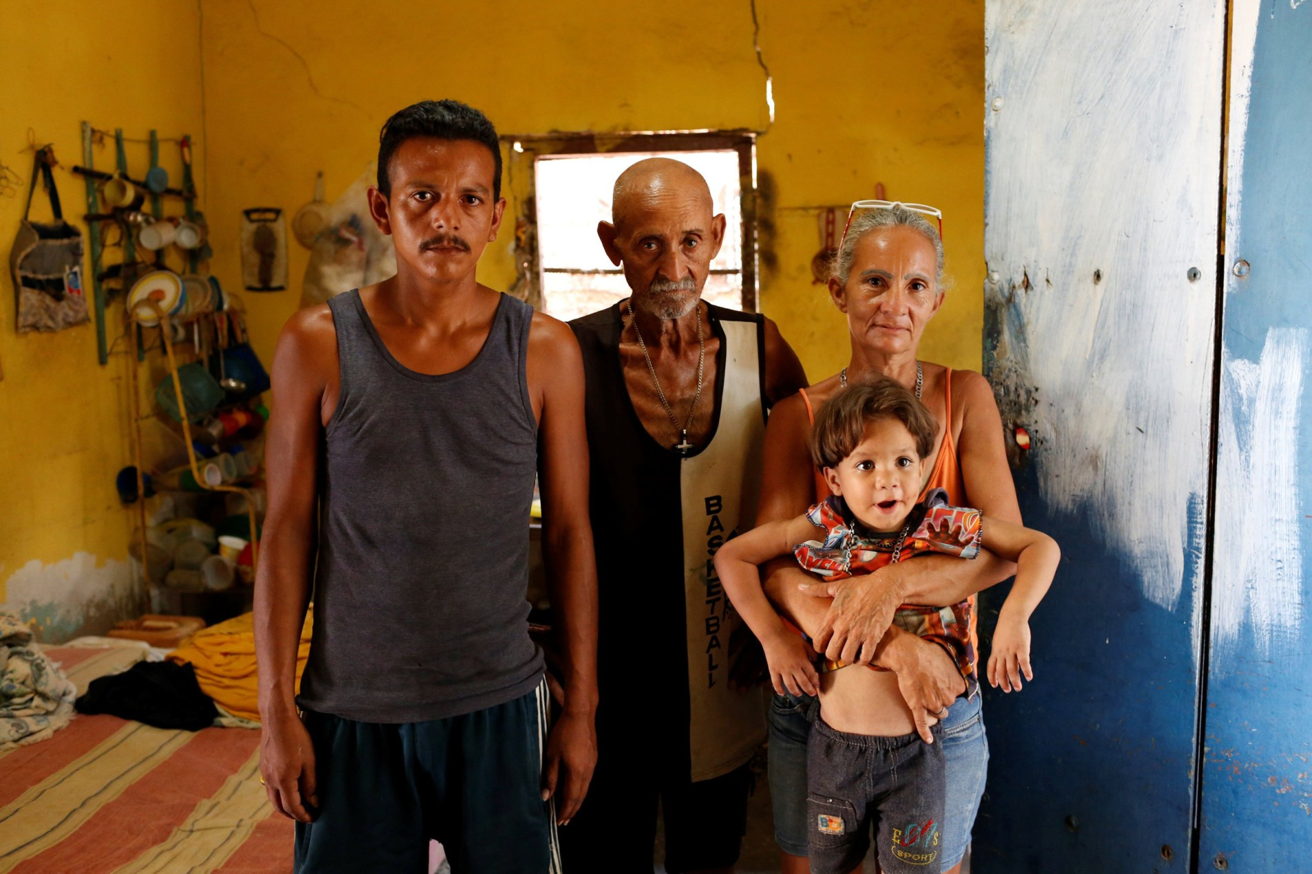 Image: Zulay Pulgar, holds her son Emmanuel, next to her husband Maikel Cuauro and her father Juan Pulgar while they pose for a portrait in their house in Punto Fijo