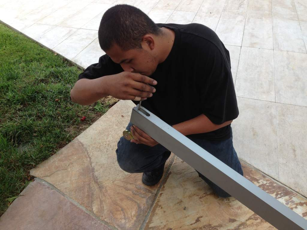 One of our techs kneeling and fixing the roller on a broken sliding door.