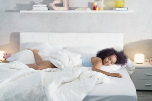 A young Black female presenting individual lays down with eyes closed and a smile on her face on a white bed with white comforter and linens.