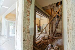 A home under construction has stripped walls and pulled bricks with contractors working on the ceiling and walls.