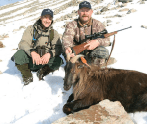 Two hunters and a dead Tahr pose for a photograph