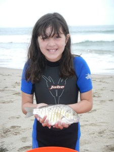 Jessica Hovey holds a nice surf perch. Catch-and-release anglers can have a blast when these fish are in the mood to bite. (TIM E. HOVEY)