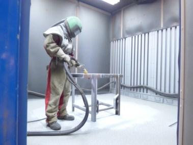 photo d'un employé de la société Calvet réalisant un grenaillage