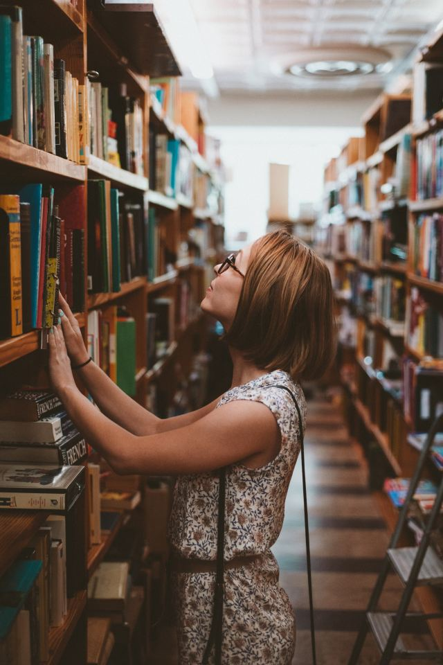 Woman looking at a shelf full of books.