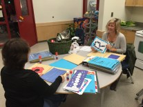 Super moms from Ms. McMillan's class putting together learning portfolios