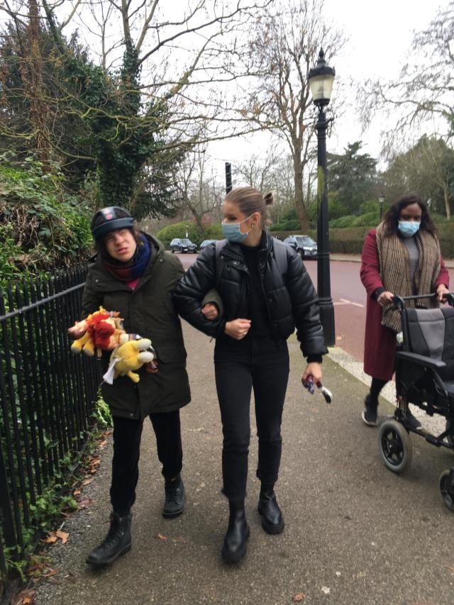 Ellie walking with her support workers.