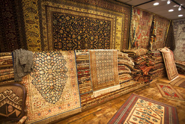 Carpet store with stacks of woven silk and Persian rugs