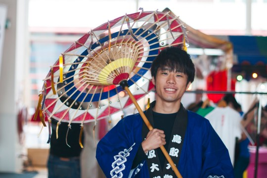 Young Japanese male in traditional dress with umbrella.