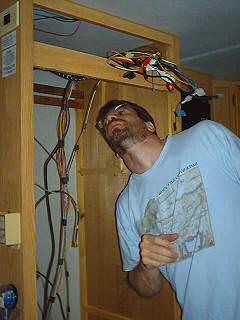 Brent examines the massive wiring for the fridge, vcr and radio stereo inside the trailer