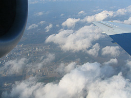 view of clouds and land outside of airplane window, photograph by Brent VanFossen