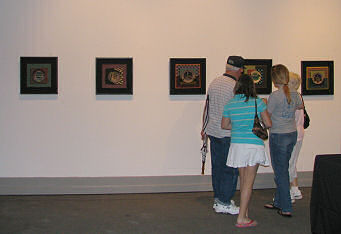Artwork Tapestry by Charlene Marsh being viewed by some of the gallery visitors