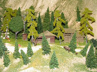 A bear wanders near a cabin in this minature mountain forest