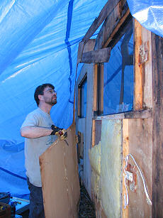 Brent removes the wall boards on the outside of our trailer slideout, photograph by Lorelle VanFossen