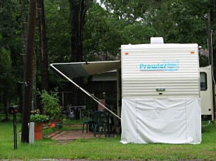 our trailer parked among trees and set up to not move in Mobile Alabama, photograph by Lorelle VanFossen